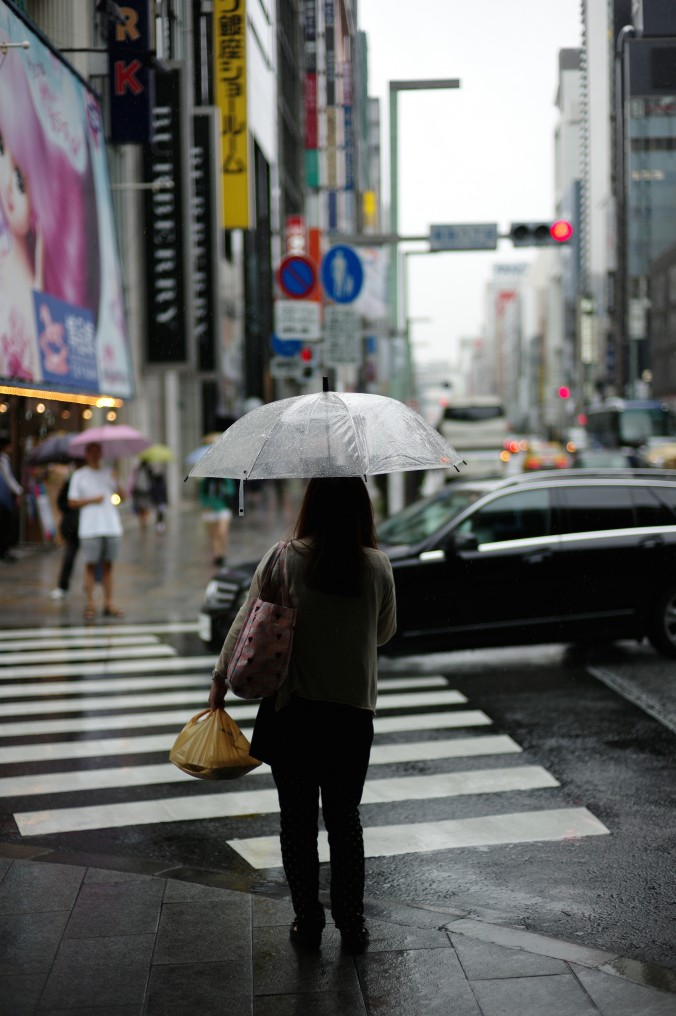back view of a woman walking in a city in the rain